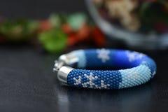 Bracelet perlé bleu avec des images des flocons de neige sur un fond foncé Photos libres de droits