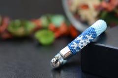 Bracelet perlé bleu avec des images des flocons de neige sur un fond foncé Images libres de droits