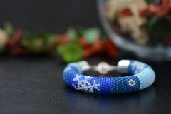 Bracelet perlé bleu avec des images des flocons de neige sur un fond foncé Images stock