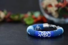 Bracelet perlé bleu avec des images des flocons de neige sur un fond foncé Photo libre de droits
