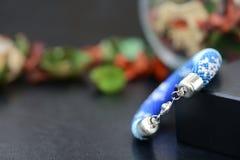 Bracelet perlé bleu avec des images des flocons de neige sur un fond foncé Photo stock