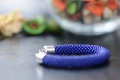 Bracelet perlé bleu-foncé sur un fond foncé Images stock