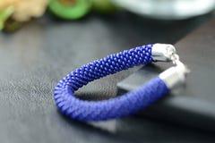 Bracelet perlé bleu-foncé sur un fond foncé Photos stock