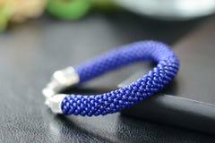 Bracelet perlé bleu-foncé sur un fond foncé Images libres de droits