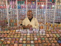 A bracelet shop in one of Indian markets. An Indian salesmen is selling beautiful traditional bracelets made of different decorative materials Stock Image