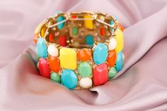Bracelet. Stylish bracelet with colorful stones on fabric background Royalty Free Stock Photography