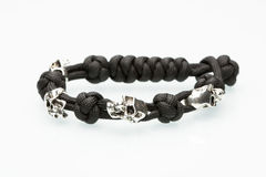 Bracelet tressé noir avec des crânes sur le blanc Photographie stock libre de droits
