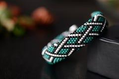 Bracelet vert de crochet de perle avec la copie celtique sur un fond foncé photo stock
