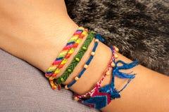 Bracelete colorido da amizade em uma mão do ` s da criança Fotografia de Stock