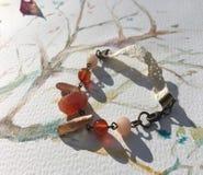 Bracelete com encantos e laço Fotografia de Stock