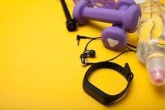 Bracelete da aptidão, fones de ouvido, pesos, uma garrafa da água e uma corda de salto Fundo amarelo imagem de stock royalty free