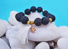 Bracelete de pedra preciosa com os grânulos da lava e a estrela do mar pretos do pendente - pedras do vulcão foto de stock royalty free