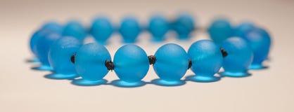 Bracelete de vidro dos grânulos azuis, foco macio Imagem de Stock