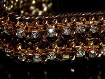 Bracelete do ouro com pedras em um fundo preto Fotos de Stock Royalty Free