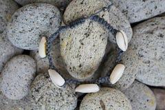 Bracelete do shell do cauri com pedras da praia imagens de stock royalty free