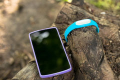 Bracelete dos esportes para as etapas de medição e o telefone esperto que encontram-se em um coto de árvore Fotos de Stock