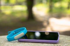 Bracelete dos esportes para as etapas de medição e o telefone esperto que encontram-se na pedra Fotografia de Stock