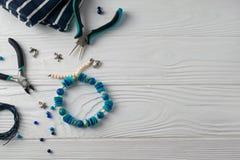 Bracelete feito a mão de turquesa, composição colocada lisa aérea com alicate, grânulos e ferramentas imagem de stock royalty free