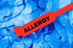 Bracelete vermelho da alergia com as luvas protetoras azuis Fotografia de Stock Royalty Free