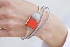 Bracelete vermelho e cinzento à moda do grânulo na mão fêmea imagem de stock