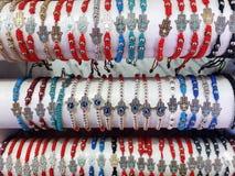 Braceletes árabes com mão e olhos azuis de Lucky Talisman Symbols Like Hamsa em um suporte do mercado imagens de stock