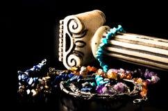 Braceletes coloridos feitos de pedras naturais e da coluna antiga no fundo preto Imagem de Stock