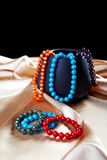Bracelets and beads on a golden fabric Stock Photography