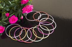 Bracelets and bouquet of roses. Colorful bracelets and a bouquet of roses on a black background Stock Photos