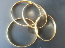 Bracelets d'or d'or sur le fond gris images stock