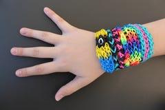 Bracelets de bande de métier à tisser sur un bras de jeune fille Photos stock