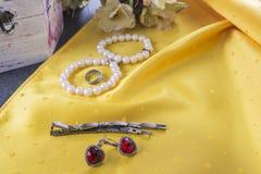 Bracelets et boucles d'oreille et anneau sur le fond jaune Image stock
