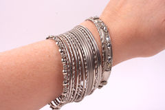Bracelets on a hand. Many silver bracelets on the wrist of a women stock photos
