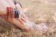 Bracelets Handcrafted sur des jambes d'une femme et des mains, bijoux de dreamcatcher Photographie stock libre de droits