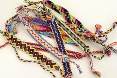 Bracelets naturels de l'amitié, bracelets tissés colorés d'amitié, fond de neige, couleurs d'arc-en-ciel, modèle à carreaux photographie stock libre de droits