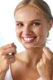 Braces på en vit bakgrund Kvinna med härligt leende genom att använda Floss för tänder arkivfoton