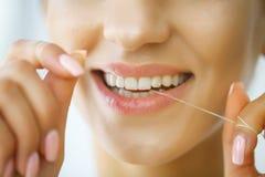 Braces på en vit bakgrund Kvinna med härligt leende genom att använda Floss för tänder H fotografering för bildbyråer
