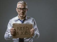 Brach den arbeitslosen Geschäftsmann, der ein Pappzeichen hält Stockbild