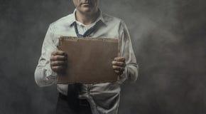 Brach den arbeitslosen Geschäftsmann, der ein Pappzeichen hält Stockfotos