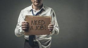 Brach den arbeitslosen Geschäftsmann, der ein Pappzeichen hält Stockfoto