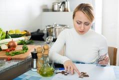 Brach Frau mit Geld und Rechnungen in der Küche Stockfotos
