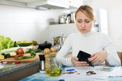 Brach Frau mit Geld und Rechnungen in der Küche Lizenzfreie Stockfotografie
