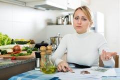Brach Frau mit Geld und Rechnungen in der Küche Lizenzfreie Stockfotos