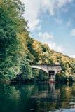 Brach Steinbrücke in einem Fluss Stockbild