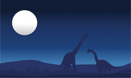 Brachiosaurus and moon silhouette Stock Images