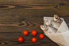 Brachsenlüge mit drei Trockenfischen auf einem dunklen Holztisch stockfotografie