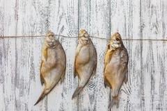Brachsenlüge mit drei Trockenfischen auf einem hellen Holztisch stockbilder
