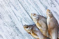Brachsenlüge mit drei Trockenfischen auf einem hellen Holztisch lizenzfreie stockfotografie