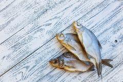 Brachsenlüge mit drei Trockenfischen auf einem hellen Holztisch stockfotografie