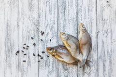 Brachsenlüge mit drei Trockenfischen auf einem hellen Holztisch lizenzfreie stockfotos
