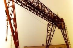 Brachte großer Portalkran des industriellen Eisens Metallmit einem Haken an den Unterstützungen für anhebendes und transportieren stockfotografie